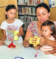by: David F. Ashton Akilah Johnson helps daughters Michela and Kalina Gravel with their paper lantern crafts.