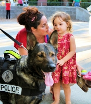 "by: David F. Ashton Elli Fae Stuart and April Eriel meet Milwaukie Police K-9 ""Jag"" at the Hawai'ian-themed concert."