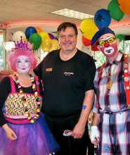 by: Rita A. Leonard At its S.E. Powell Boulevard at 26th Street location, Burgerville Manager Paul Ridlon is flanked by clowns