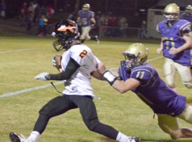 by: John Brewington ON THE MOVE—Scappoose's Paul Revis is dragged down by Astoria's Conor Harber during Friday's game in Astoria.