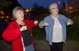 by: VERN UYETAKE Diana Hughes, left, and Margaret Matthies get  inspired to perform the chicken dance while listening to the music of the Oom Pah Boys Friday night at the West Linn Oktoberfest celebration.