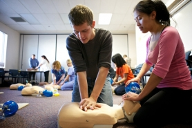by: JAIME VALDEZ Micah Taylor practices chest compressions on a mannequin as Eline Halvorson assists at the CLIMB Center for Advancement, run by Portland Community College for professional and business development.