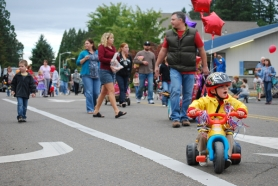 by: Geoff Pursinger Hundreds of Metzger residents march down Locust Street during Saturday's centennial parade.