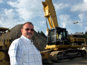 by: Jim Hart John Sayles, president of Konell Construction and Demolition Corporation in Sandy, stands in front of some of the company's track-laying equipment: a dozer, left, and a million-dollar excavator with an arm that reaches 95 feet into the air.