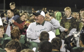 by: DAN BROOD CELEBRATION TIME — Tigard High School coach Craig Ruecker celebrates with the Tiger players and fans following the team's 35-7 win over Tualatin.