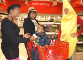 by: staff photo by ANNE ENDICOTT From left, Chanice McDermott, Alycia Monttoya (in hat) and her son, John, 2,  are greeted by  Banana-man, AKA Cameron Sulkosky, Fairview Target manager. The women recently moved to Gresham from California and were thrilled to find the expanded grocery.