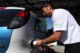 by: JAIME VALDEZ Roger Yasukawa, an account director at Trivalle Communications USA, plugs  the new Mitsubishi electric car into the solar-powered charging station at the Oregon Museum of Science and Industry.