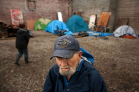 by: CHRISTOPHER ONSTOTT A man who identified himself as Thurman prepares to pitch his tent at the  