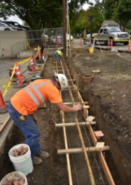 by: VERN UYETAKE Duane Bates of Brown Contracting prepares to install a retaining wall on the west side of State Street at North Shore Road, with Jason Bates, also of Brown Contracting, doing the same in the background. Construction crews are working to improve safety and aesthetics at the intersection.