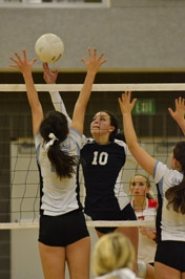 by: VERN UYETAKE Lake Oswego's Nikki Spathas tips a shot over a Lakeridge blocker in Tuesday's four-set win over the Pacers.