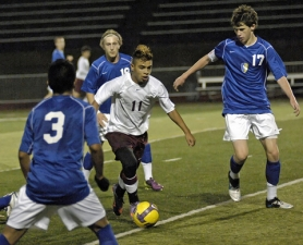 by: DAN BROOD SURROUNDED — Tualatin sophomore Damien Cortez-Garcia (11) looks to drive past Newberg's (from left) Jeber Minquez, Spencer Snyder and Ryan Linquist in last week's match. The Wolves won 5-1.