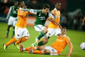 by: CHRISTOPHER ONSTOTT Sal Zizzo of the Portland Timbers gets tripped up by the Houston Dynamo defense in Friday night's 2-0 Portland loss at Jeld-Wen Field.