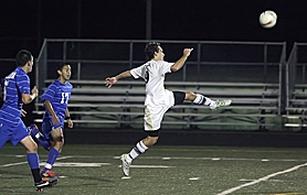 by: Miles Vance UP AND OVER — Southridge's Sam Albert — trailed by Aloha's Edgar Rivera and Juan Ramirez — chips a shot over the Warrior keeper for a goal on Monday.