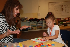 by: Christina Lent Emily earns praise after she successfully finds letters to spell her name during the Leap Start Summer Academy at Barnes Elementary School.