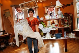 by: Shanda Tice Carrie Dorn shows off a vintage formal dress and purse while preparing her new antique store, The Victorian House, for opening day Nov. 1. The store is located at 343 Main Ave. in downtown Gresham.