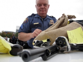 by: peter Korn Portland Police Sgt. Tim Sessions displays some of the 43 guns turned in Saturday at a Ceasefire Oregon event aimed at removing weapons from the street.