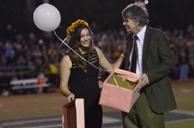 by: Vern Uyetake The big moment came at halftime of Friday night's football game against West Linn when Colleen Condon opens her box with the white balloon that signified that she was this year's homecome queen. Condon was escourted by her dad John Condon.