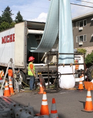 by: David F. Ashton Portland Bureau of Environmental Services contractor employees feed the pipe lining down into the Sellwood sewer line.