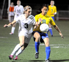 by: MATTHEW SHERMAN West Linn's Alexy DaHarb battles with Aloha's Linda Nguyen for a loose ball in Tuesday's 3-1 victory. DaHarb assisted on the Lions' first goal of the game.