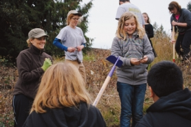 by: Stover E. Harger III HANDS ON — students and volunteers gather around fifth-grader Sydney Kratky as she shows off a garter snake she found while helping plant trees at the Sauvie Island Academy Oct. 28.