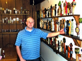 by: Jim Hart Trout Pub owner Tom Dunn stands near some of the tap handles for microbrews that he often has on tap among the 19 kegs he taps. Dunn and his family have taken over ownership of the long-standing Sandy business.