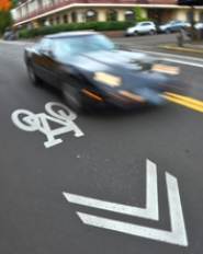 "by: VERN UYETAKE  A ""sharrow,"" the symbol painted here, provides a reminder to those on the road that bicycles and cars share the pavement. In addition to new signage, sharrows will aim to increase safety and mark the path for cyclists traveling the new Iron Mountain Bikeway planned in Lake Oswego."