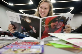 by: CHRISTOPHER ONSTOTT High school student Jessica Buchanan looks over stacks of literature for a variety of colleges on Monday at the Portland National College Fair, which drew large crowds from around the Portland area. This week is