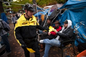 by: Christopher Onstott Portland police handed out information Thursday about the upcoming closing of Chapman and Lownsdale squares in downtown Portland. The two public parks have been home to the Occupy Portland camp since Oct. 6 All of the campers will be evicted from the camps after 12:01 a.m. Sunday.