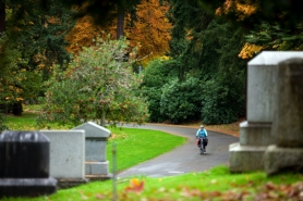 by: CHRISTOPHER ONSTOTT A cyclist rides the path through River View Cemetery adjacent to 146 acres of undeveloped land partly purchased by the Portland Bureau of Environmental Service, a transaction that may soon end up in court.