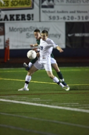 by: VERN UYETAKE Kyle Gazzigli shields a Jesuit defender in Lake Oswego's 4-1 quarterfinal victory over the Crusaders last week.