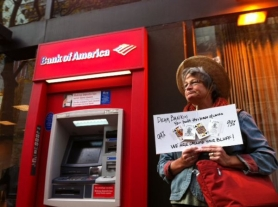 by: Jaime Valdez Kathy Carpenter of Vancouver, Wash., stands in protest outside a downtown Portland Bank of America ATM during Thursday's day of action organized by the Occupy Portland movement. Protesters marched on several banks during the day to protest foreclosure issues and economic inequality.
