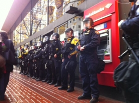 by: Jaime Valdez Police in riot gear stand in front of a downtown Portland Bank of America branch during Thursday's N17 Day of Action that attracted hundreds of people to protest rallies and marches. About 50 people were arrested during the daylong protest.