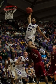 by: STEVE GIBBONS Kevin Bailey, a 6-5 freshman for the University of Portland, goes high and hard to the basket on a dunk attempt late in Sunday's home game with Washington State.