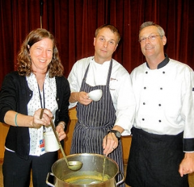 by: Elizabeth Ussher Groff Genoa Restaurant chef David Anderson ]center), student teacher Kristina Engstrom, and parent Kevin McConville, together serve pumpkin-rice soup at the Meriwether Lewis Elementary School Fall Harvest Dinner on October 21st.