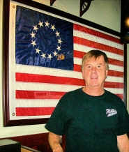 by: Rita A. Leonard Steve Moore, owner of Philadelphia's Steaks & Hoagies in Westmoreland, stands beside a replica of our country's first flag.