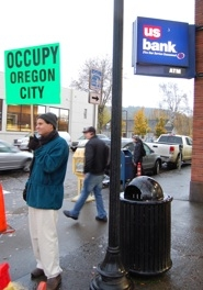 by: raymond rendleman Chris Hofgren protests in front of a bank along Main Street in downtown Oregon City.
