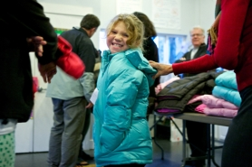 "by: Jaime Valdez Jasmine Linder, 8, smiles as she puts on a new coat during ""Operation Warm"" at Greenburg Oaks apartments in Tigard. The coats were donated by the Tigard Rotary clubs to keep kids healthy and warm during the cold winter months."