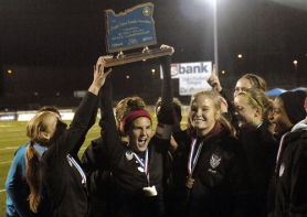 by: DAN BROOD STANDING TALL — Tualatin senior Anna-Marie Popma holds up the state championship trophy following Tualatin's 1-0 win over Sunset.