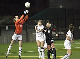 by: Miles Vance IN THE FINALE — Sunset goalkeeper Taylor Luty punches the ball away while teammate Kristen Jondahl and Tualatin's Megan Freel close in on Saturday night.