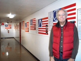 by: Contributed photo Michael Orelove, a member of the Kiwanis, organized the recent flag project at Troutdale Elementary School and stands in the new 'Hall of Flags.'
