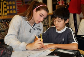 by: barb randall Colleen Condon helps Silas Brady make corrections on an assignment. The two work together afterschool each Monday.