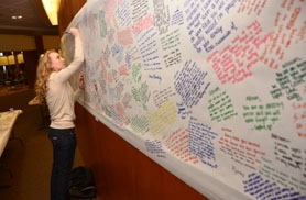 by: VERN UYETAKE LOHS senior Ariel Tamblyn, above,  writes a message on the memorial set up at the high school.