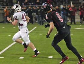 by: DAN BROOD HE'S GONE – Sherwood senior fullback Travis Dyer (left) sprints past Mountain View's Cody Hollister on his way to scoring on a 32-yard run in the second quarter of Saturday's Class 5A state championship game.