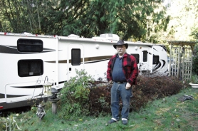 by: Jeff Spiegel John Nieder stands in front of his temporary home, a trailer that is parked in his driveway while his old house is being rebuilt.