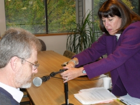 "by: BARB RANDALL Cyndie Glazer adjusts the microphone for John Harris, public works manager for the city of Lake Oswego. He was one of 50 people who read sections of ""Mink River"" to create an audiobook for the Lake Oswego Reads program."