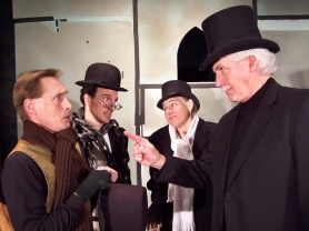 "by: Kelly Lazenby Scrooge, played by Curt Hanson, scolds Bob Cratchit, played by Scott Caster, in the Nutz-n-Boltz production of ""Jacob Marley's Christmas Carol."" Watching the duo are Marley, played by Justin Lazenby, and the Bogle (ghost), portrayed by Megan Murphy Ruckman."