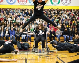 "by: John Schrag Forest Grove High sophomore Patrick Barrios leaps over Makenna Sewell's wheelchair during Michael Jackson's song ""Thriller"" in Friday's lip-sync contest."