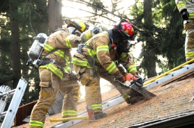 by: Vern Uyetake From left, Jeremy Langeliers, a Lake Oswego Fire Department paramedic, and Dan Carpenter, lieutenant, work to vertically ventilate a house during a recent training exercise.