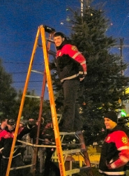 by: Courtesy of Mary Afarsi-Howard Firefighters from Woodstock's Station 25 on 52nd helped string the lights on the Woodstock Boulevard community Christmas Tree on December 3rd.