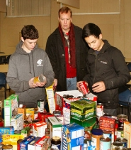 by: David F. Ashton Scoutmaster Tom Gustafson watches as Cleveland High School sophomore Carter Krevanko and Grant High freshman Caleb Walcott — both Boy Scouts — help sort the collected non-perishable food.